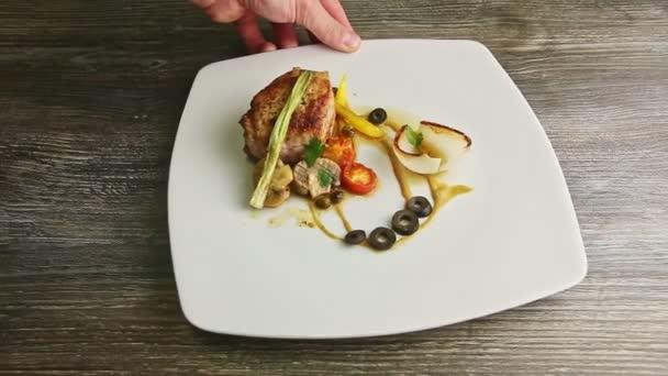 lidská ruka otáčí původní talíř se smaženým masem a grilovanou zeleninou