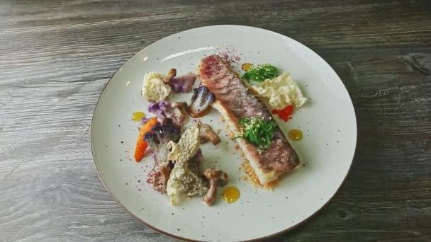 lidské ruce uřízly malý kousek z pečeného rybího filetu vidličkou a nožem na talíři