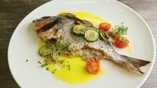 finom egész sült hal és zöldség forog a tányéron