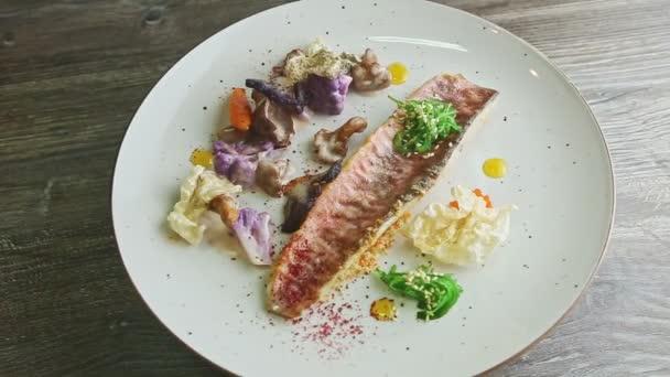 pohled shora na trendy zdobené pečené rybí filety s nakrájenou zeleninou rotuje na talíři