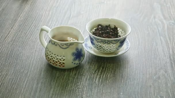 closeup white porcelain teapot with tea leaves and kettle with hot tea