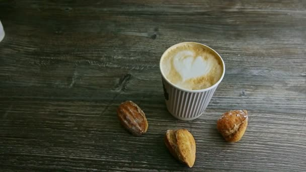 man hand put cup with cappuccino next to another and almond cookies