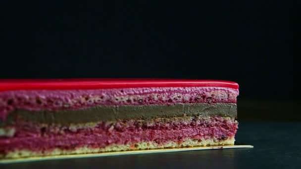 closeup panorama on portion of pink glazed multi-layered chocolate cake