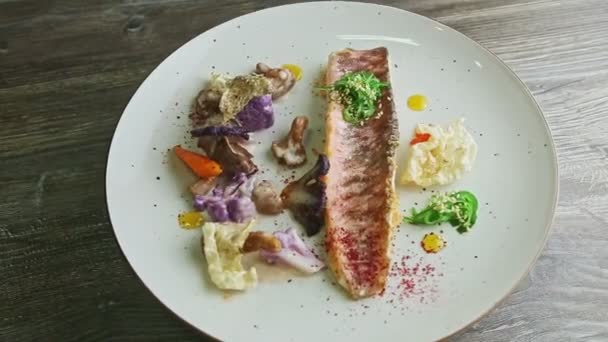 top view on finely decorated grilled fish fillet with sliced vegetables rotates on plate
