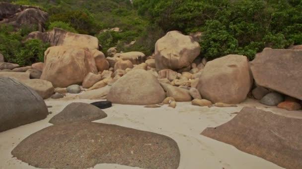 Pohyb po hromadě skal na písečné pláži u úpatí kopce