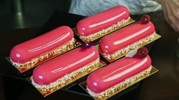 lila virággal történő díszítés folyamata az öt rózsaszín mázas ovális sütemény egyikén, amelyeket kókuszdióhagymával és málnával díszítenek arany standokon