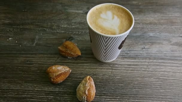 man hand put second latte cup next to another and manmond cookies