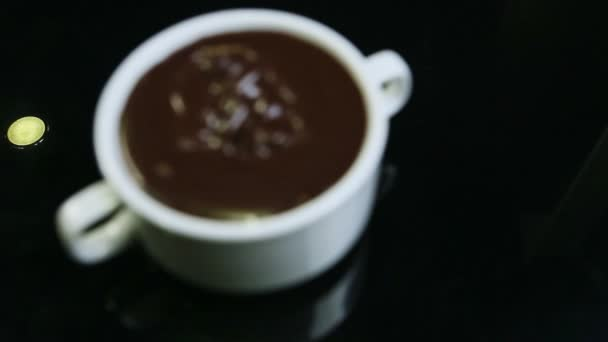 focus in on big white round cup with two handles filled with melted dark chocolate