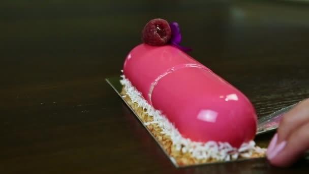 a cukrász késsel elviszi a rózsaszín málnás ovális torta felét