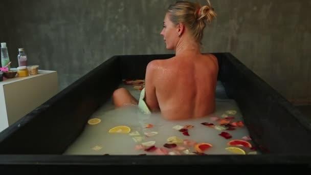 mladá blondýnka dívka myje záda v černé lázni s mlékem, okvětními lístky růží a citrusy