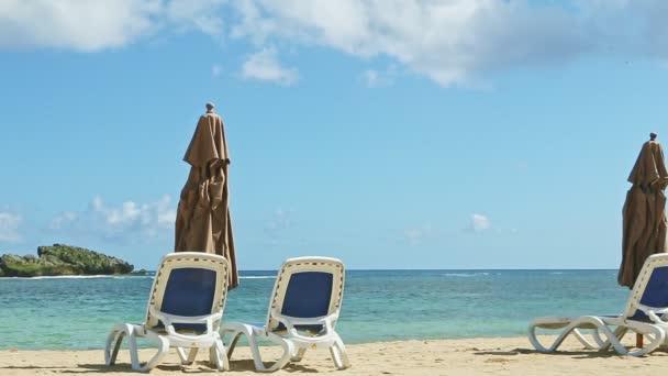 pomalu panorama na prázdném písčitém pobřeží oceánu s plážovými židlemi a zavřenými slunečníky