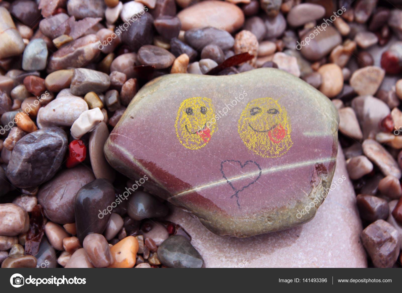 Smiley verniciato sulla ghiaia bagnata, bagnata pietre di mare ...