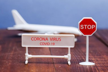 Corona virus sign on foreground with toy aeroplane in back