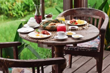 Yummy and healthy breakfast on terrace on wood table with beautiful view