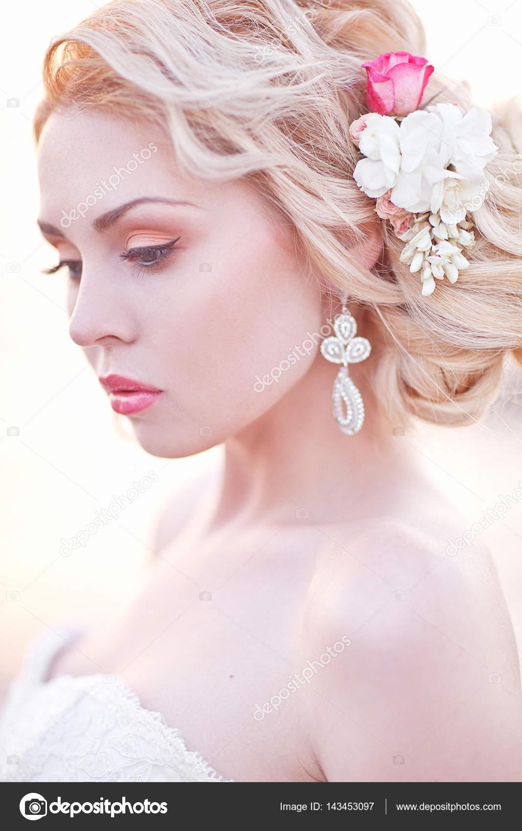 Novia morena joven en vestido blanco posando junto al mar en ...