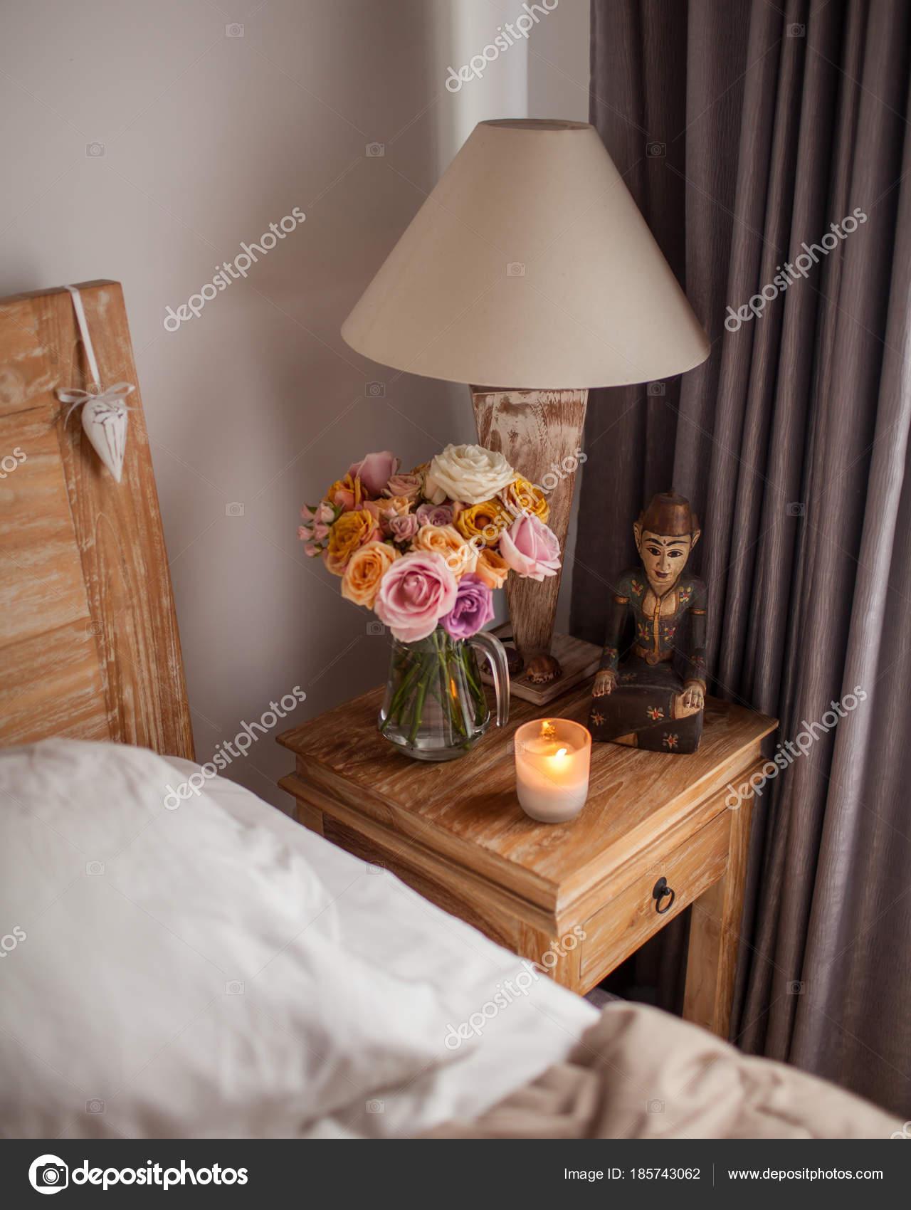 Ein Nachttisch Neben Dem Bett Mit Einer Lampe, Ein Blumenstrauß Aus Rosen,  Kerzen Und Handcreme U2014 Foto Von April_89