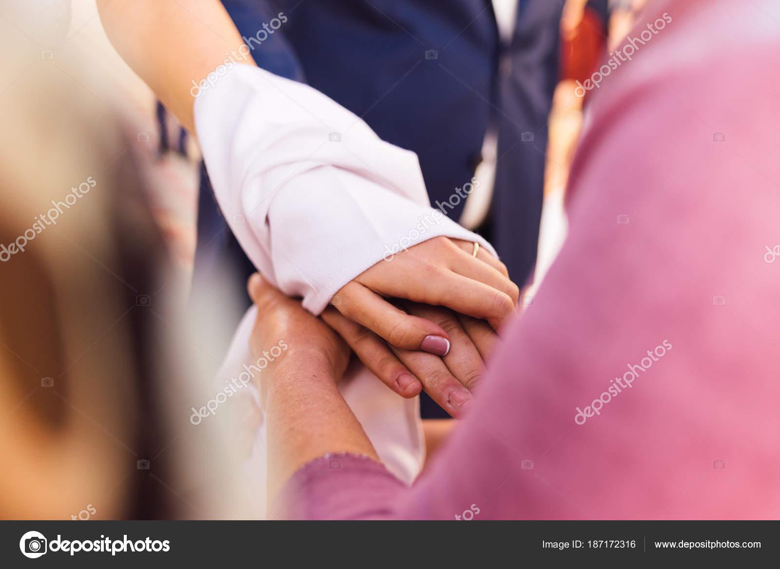 Las manos de la novia y el novio están vinculadas con una toalla ...