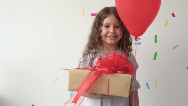 Egy kislány, kezében egy nagy dobozzal, piros masnival. Aranyos mosoly és félénk. Ünnepnap.