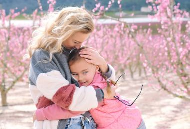 Mother and daughter in a grove of fruit trees