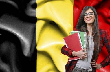 Happy female student holdimg books against national flag of Belg