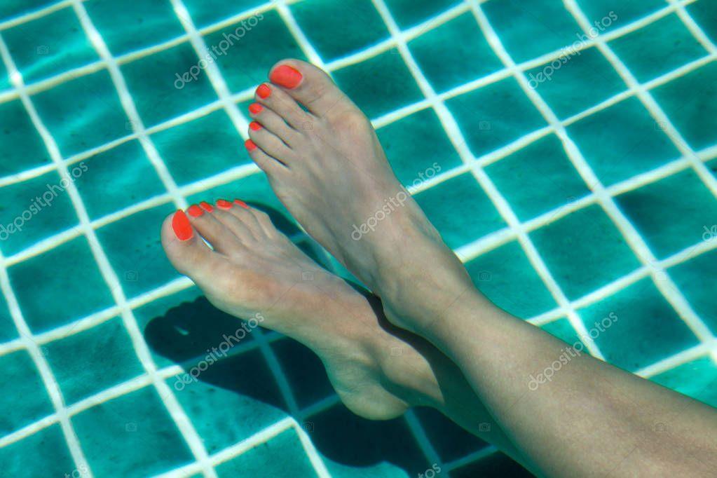 Piedi femminili con lo smalto rosso su unghie imbevuto in for Piani di fattoria di 2000 piedi quadrati