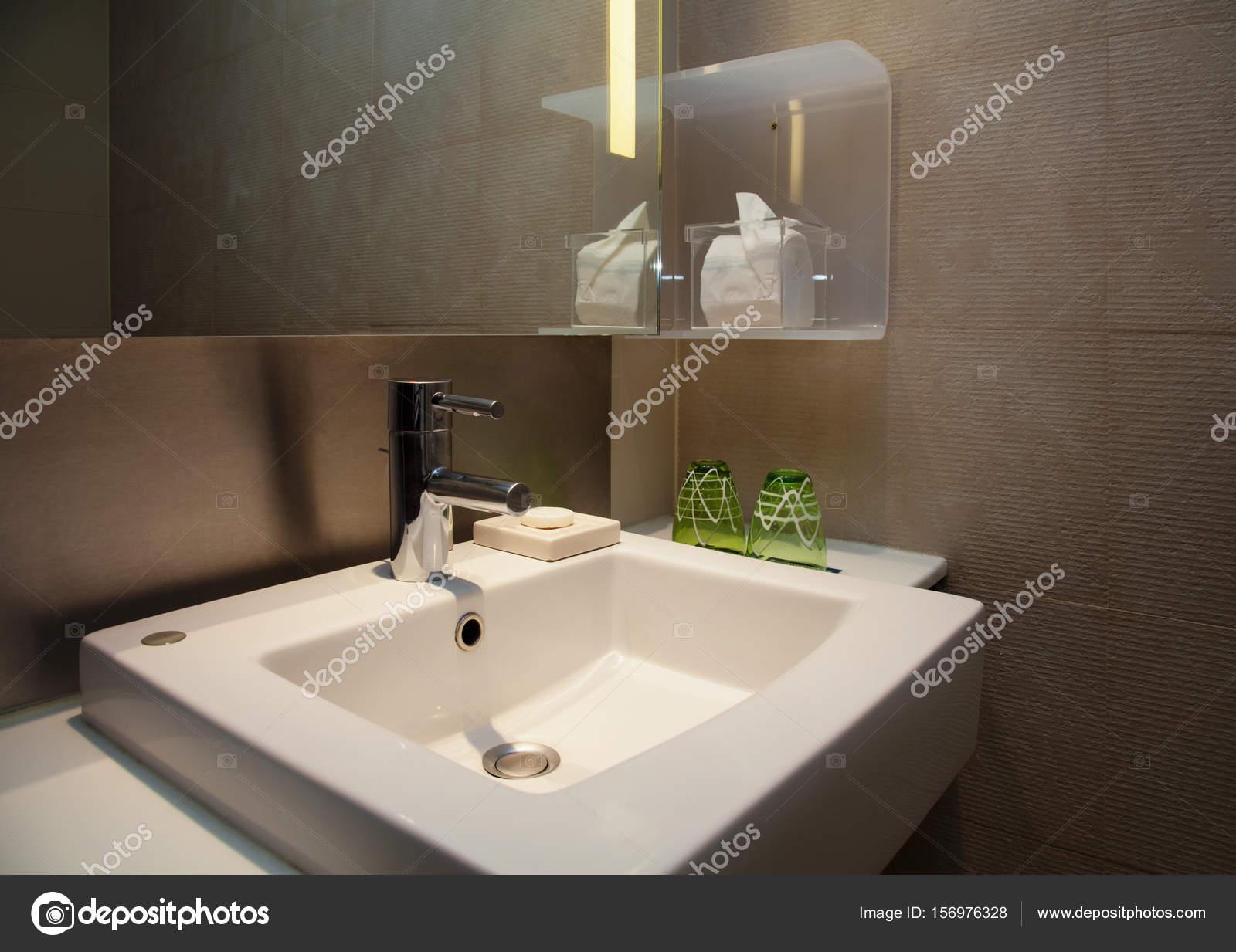 Waterkraan en keramisch wit wastafel in een moderne wc met bruine