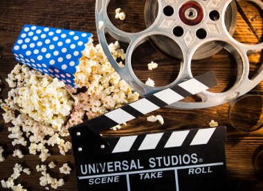 Cinema concept of vintage film reel with popcorn on old wooden background. stock vector