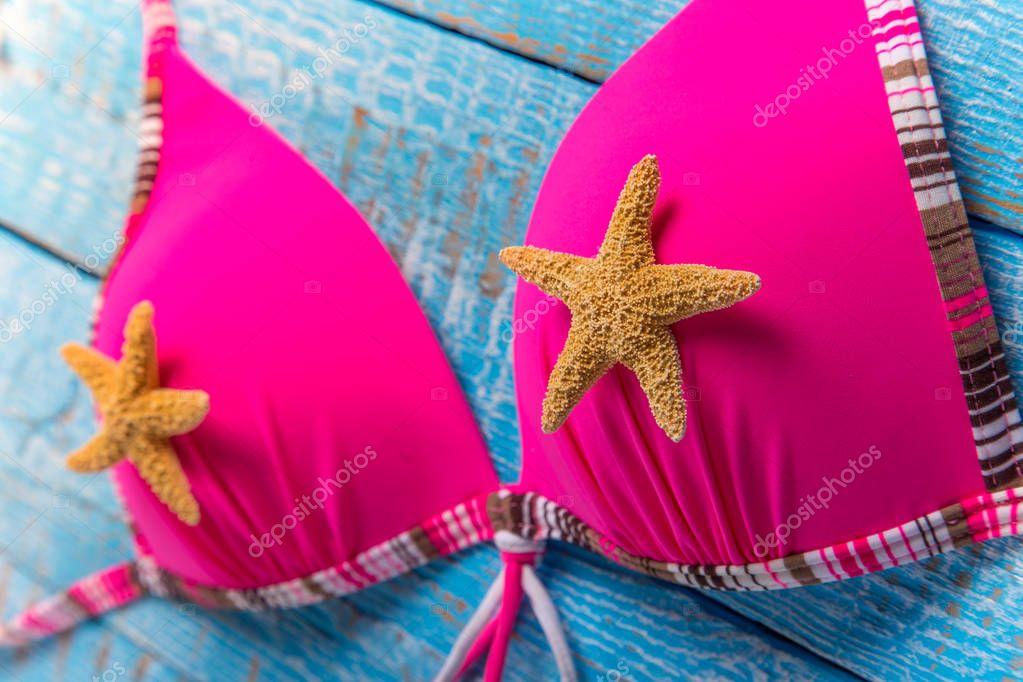 Beauty pink bikini on rustic wooden table.