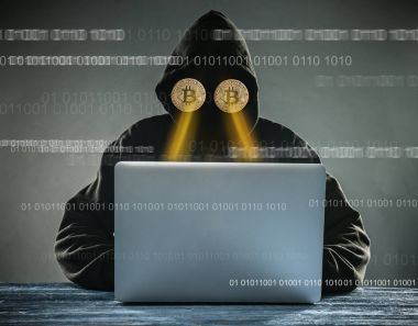 Anonymous person sitting behind laptop having gold bitcoins instead of eyes