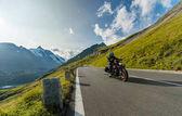 Řidič motocyklu Jízda křižník japonského vysokého výkonu v alpské dálnice na slavné Hochalpenstrasse, Rakousko.