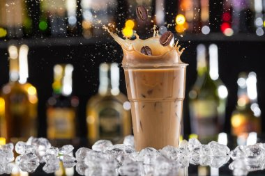 Cold coffee drink with ice, beans and splash.