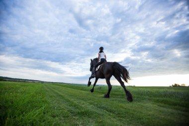 Beautiful woman riding a black friesian horse.