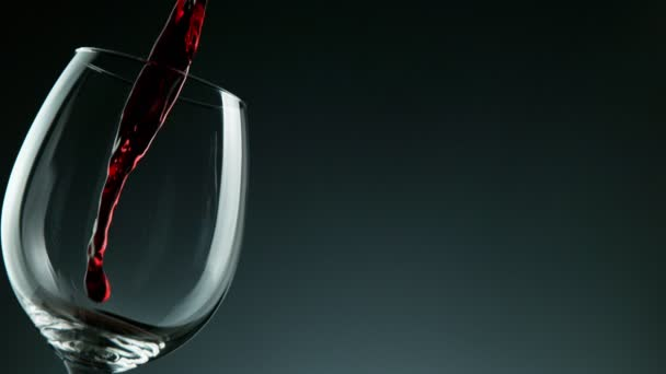 Super Slow Motion Detail Shot of Pouring Red Wine from Bottle on dark Background.