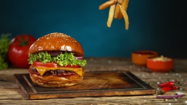 Hranolky padají vedle cheeseburgeru, ležícího na dřevěné prkně. Super zpomalený pohyb