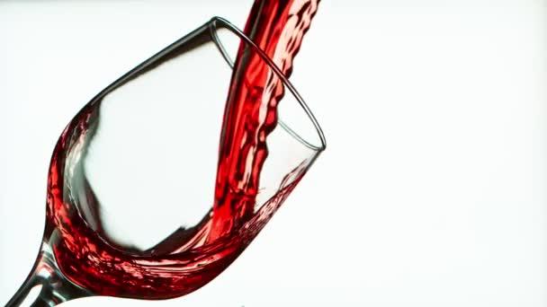 Super Slow Motion Részlet lövés öntő vörösbor palack fehér háttér.