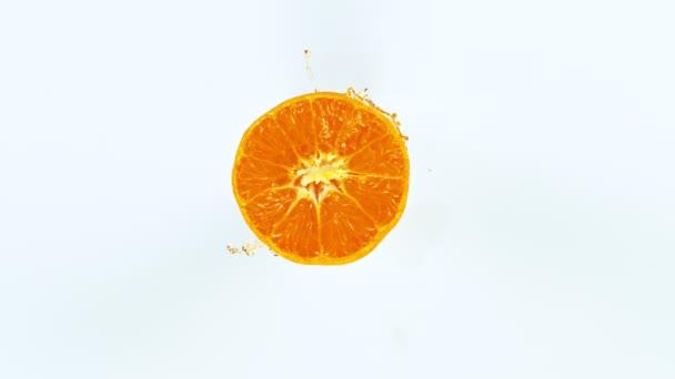 Super Slow Motion Shot of Tangerine Slice with Splashing Juice Isolated on White Background