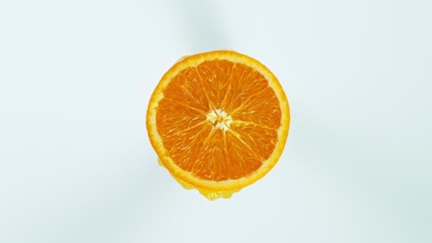 Super Slow Motion Shot of Orange Slice with Splashing Juice Isolated on White Background