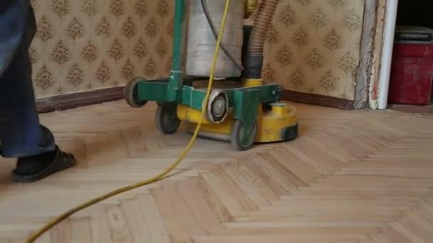 Dělník, leštění staré dřevěné parketové podlahy s brusky
