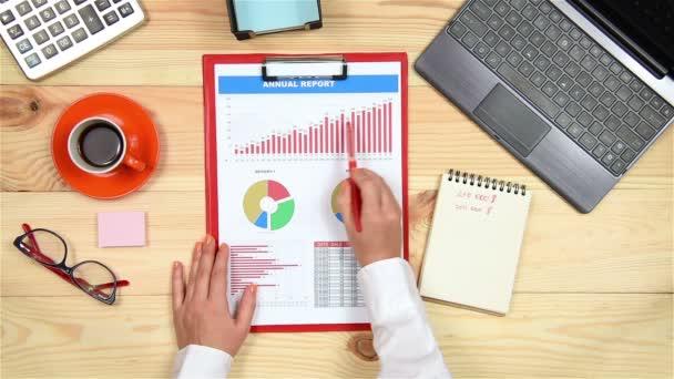 Obchodník ruce analyzuje různé finanční grafy na stole. Pohled shora