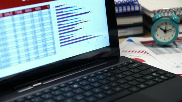 Office Desktop With Laptop And Stock Exchange Statistics On Table