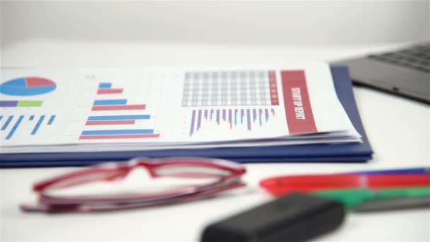 Office Desktop With Business Items, Stock Exchange Statistics, Laptop, Pen And Red Glasses