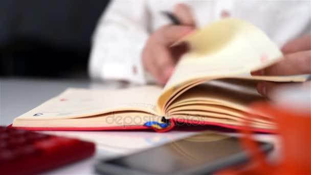 Podnikatel, práce v kanceláři a pořizování poznámek v deníku. Detailní záběr