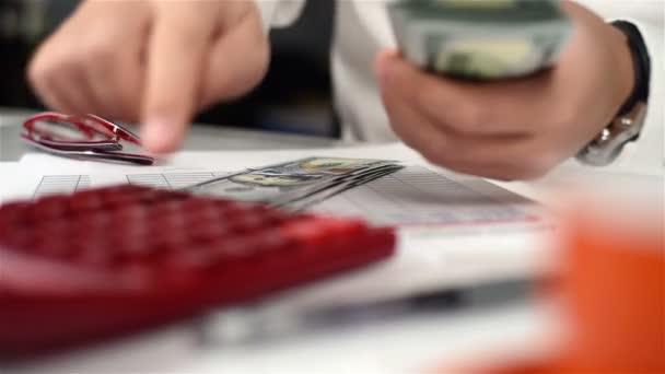 Uomo di ragioniere con calcolatrice conta i dollari. Concetto di operazioni bancarie. Chiuda in su