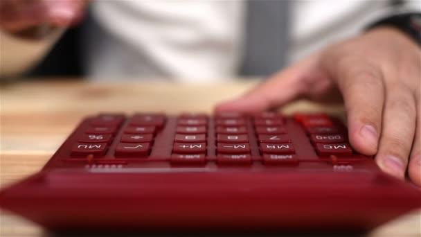 Účetní ručně pomocí červená kalkulačka. Obchodní koncept. Detailní záběr