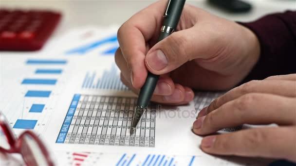 Obchodník muž s perem v ruce a analyzuje burze statistiky