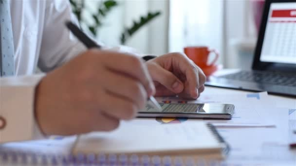 Businessman Hand With Financial Charts On Mobile Phone Drawing Stock Data In Notepad
