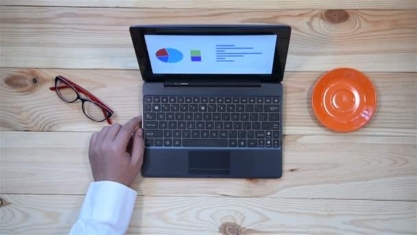 Üzletember dolgozik az irodában, kávé italok és gépelés-On Laptop. Nézd meg felülről