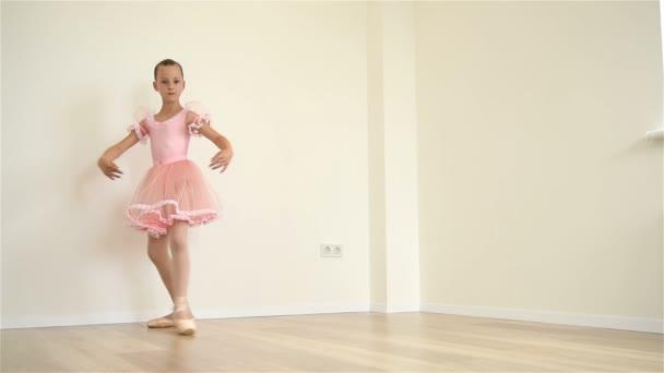 junge Ballerina im rosa Kleid beim Workout im Zimmer. Zeitlupeneffekt