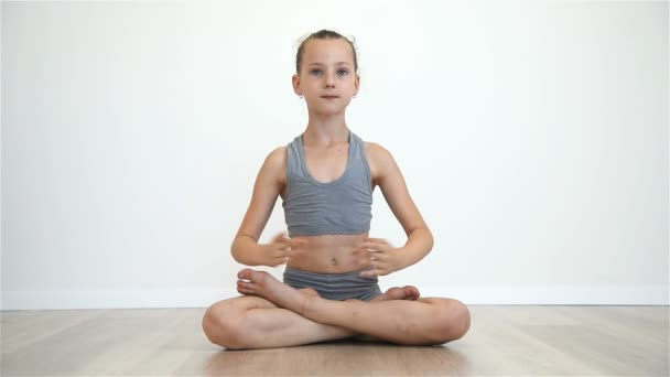 Malá holčička dělá Namaste sedí na podlaze v lotosové pozici. Efekt zpomaleného pohybu
