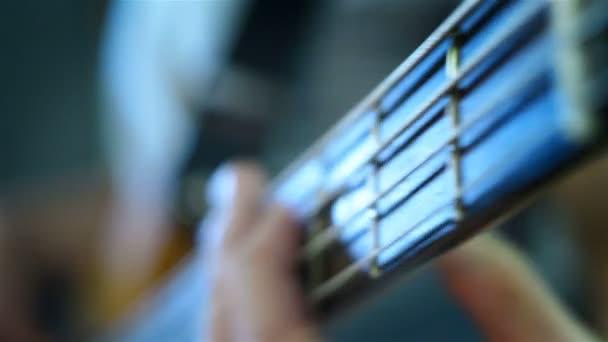 Basszus gitáros, elektromos gitáron játszik. Közelről